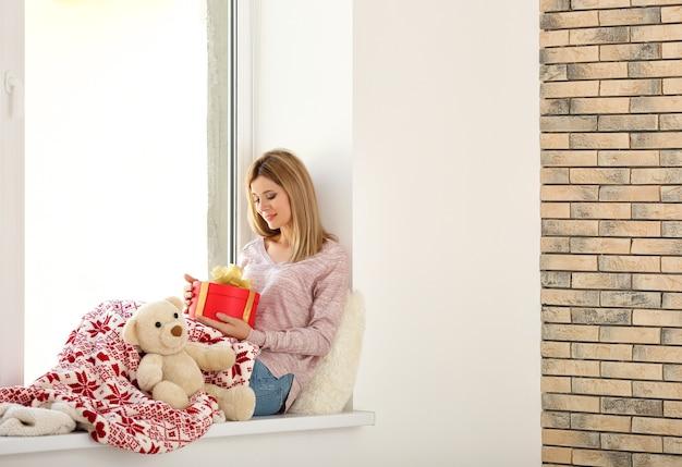 Giovane bella donna con confezione regalo seduta sul davanzale della finestra. concetto di vacanza di natale
