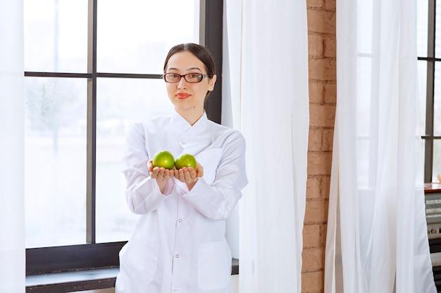 Giovane bella donna con gli occhiali in camice da laboratorio che tiene le mele verdi vicino alla finestra.
