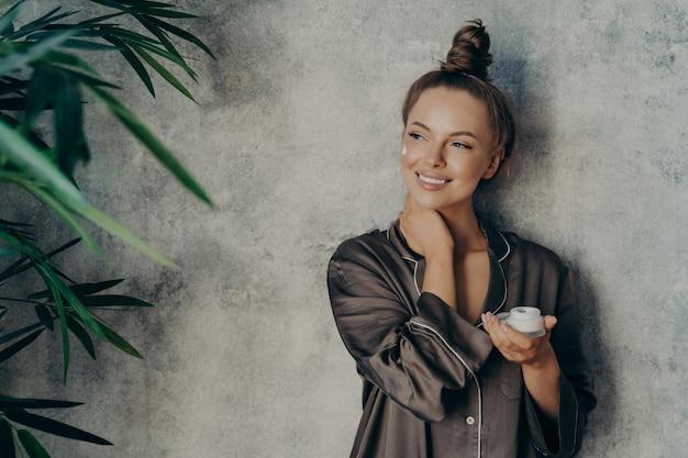 Giovane bella donna con una pelle sana e luminosa che sorride ampiamente mentre tiene in mano una crema per il viso