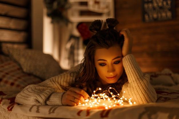 Giovane bella donna con luci natalizie in maglione retrò lavorato a maglia sul letto