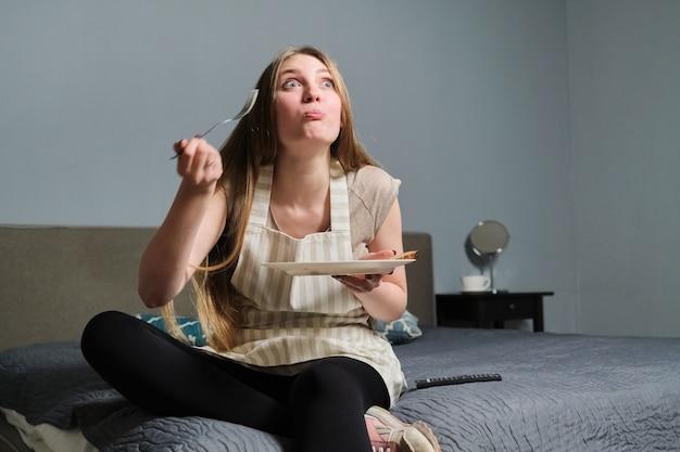 Giovane bella donna con interesse a guardare la tv e mangiare