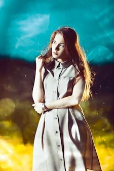 Giovane bella donna con i capelli lunghi sulla parete scintillante