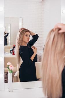 Giovane bella donna con capelli biondi lunghi sani