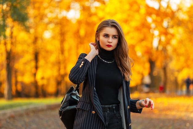 La giovane bella donna con le labbra rosse in un vestito elegante alla moda con una giacca e un maglione con uno zaino cammina in un parco autunnale con fogliame autunnale luminoso al tramonto