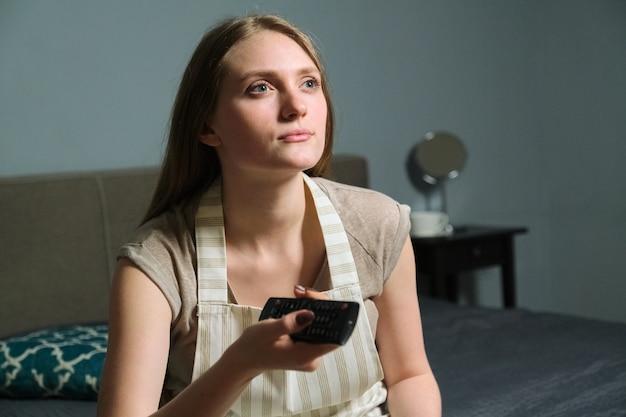 Giovane bella donna con telecomando, donna seria seduta a casa