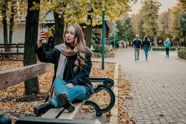 Giovane bella donna con la tazza di caffè riutilizzabile nel parco