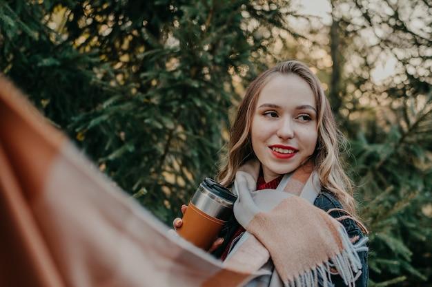 La giovane bella donna con la tazza di caffè riutilizzabile cammina nel parco