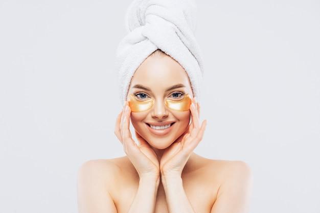 Giovane bella donna con un asciugamano sulla testa