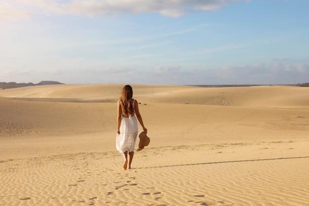 Giovane bella donna con vestito bianco che cammina tra le dune del deserto durante il tramonto. ragazza che cammina sulla sabbia dorata su corralejo dunas, fuerteventura.
