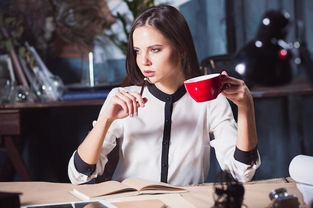 Giovane bella donna che lavora con una tazza di caffè e un taccuino in ufficio loft