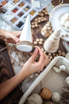 Giovane bella donna che avvolge un cono di schiuma con spago o filo e realizza alberi di natale di diverse dimensioni per la decorazione della tavola. concetto di preparazione per festività e feste.