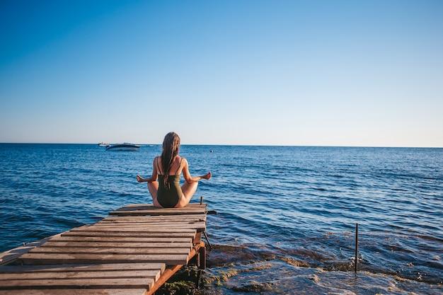 Giovane bella donna sullo yoga sulla spiaggia