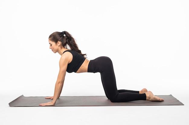 Posa di yoga della giovane bella donna isolata sopra la superficie bianca dello studio