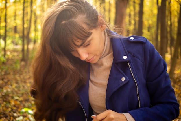 La giovane bella donna nel parco autunnale al sole splende sullo sfondo degli alberi gialli