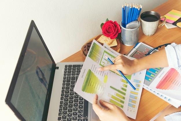 La giovane bella donna lavoratrice discute sul servizio del sito con il computer portatile della tenuta dell'uomo d'affari del collega