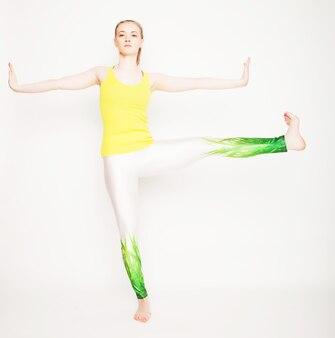 Giovane bella posa di yoga su sfondo bianco
