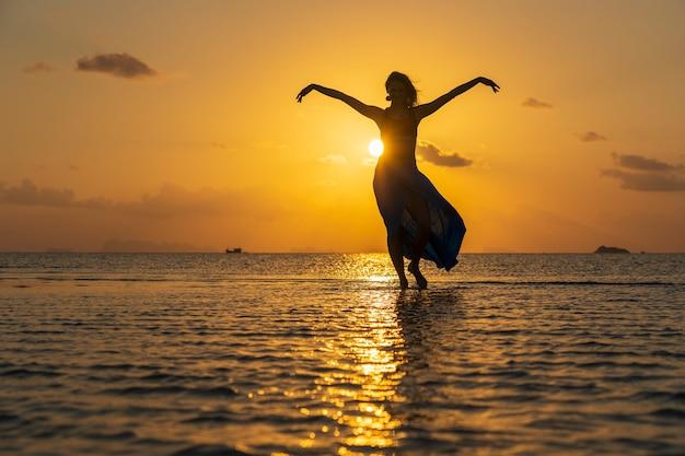 Giovane ragazza di bellezza che balla alla spiaggia tropicale sull'acqua di mare all'isola di paradiso al tramonto, thailandia, primi piani. concetto di estate. viaggio di vacanza.