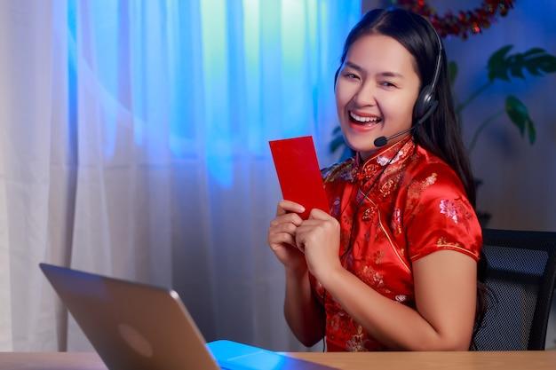 Donna asiatica felice di giovane bellezza che porta il vestito cinese da tradizione che si siede davanti al computer portatile che tiene busta rossa