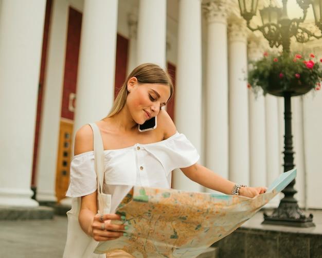 Il turista della giovane donna di bellezza esplora la mappa della città e parla al telefono nell'ambiente urbano