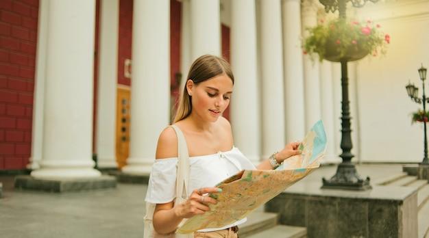 Il turista della giovane donna di bellezza esplora la mappa della città nell'ambiente urbano