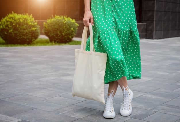 Giovane bella donna con borsa ecologica in lino sullo sfondo della città?