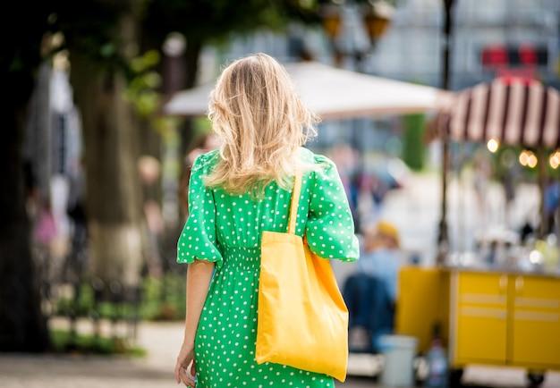 Giovane bella donna con borsa ecologica in lino giallo sullo sfondo della città?