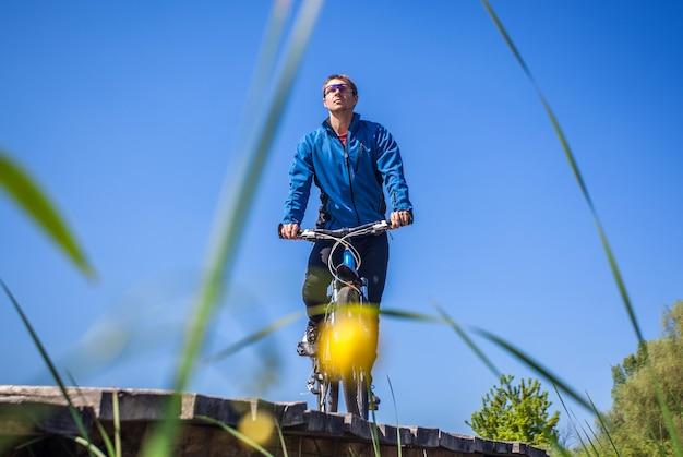 Il giovane ciclista va in mountain bike sul ponte sul fiume