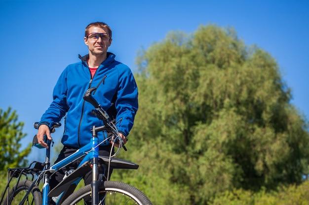 Il giovane ciclista guida una mountain bike nella foresta