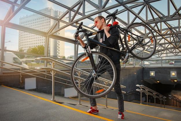 Un giovane motociclista sale le scale del sottopasso e porta in spalla una bicicletta