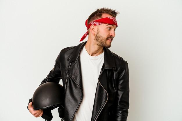 L'uomo caucasico tatuato del giovane motociclista che tiene un casco isolato su priorità bassa bianca sembra da parte sorridente, allegro e piacevole.
