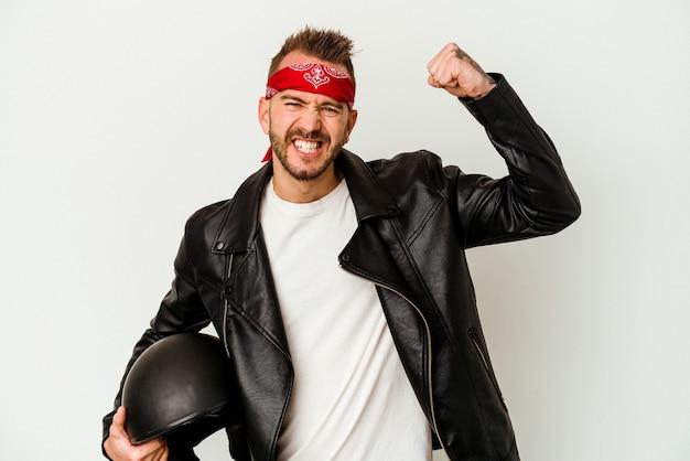 Uomo caucasico tatuato del giovane motociclista che tiene un casco isolato su priorità bassa bianca che alza il pugno dopo una vittoria, concetto del vincitore.