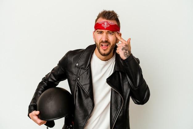 Uomo caucasico tatuato giovane motociclista che tiene un casco isolato su priorità bassa bianca che mostra un gesto di delusione con l'indice.