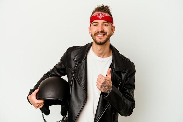 Uomo caucasico tatuato del giovane motociclista che tiene un casco isolato su fondo bianco che sorride e che alza il pollice in su