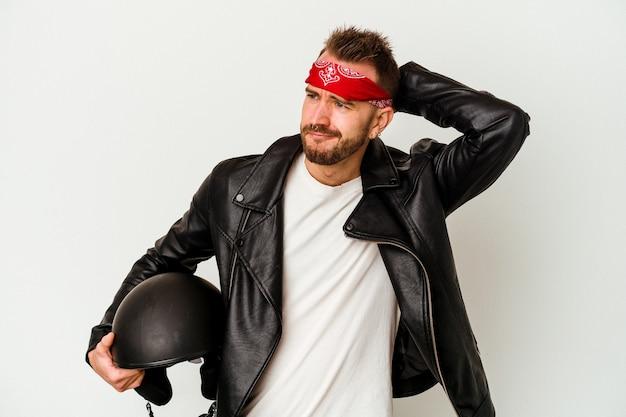Uomo caucasico tatuato giovane motociclista che tiene un casco isolato su priorità bassa bianca che tocca la parte posteriore della testa, pensando e facendo una scelta.
