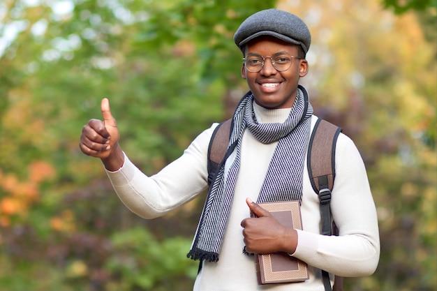 Giovane studente afroamericano africano nero, ragazzo con zaino e libro che mostra pollice in su e sorridente