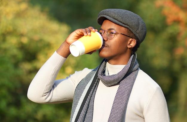 Giovane afroamericano africano nero giovane uomo che beve caffè dalla tazza di carta in un parco