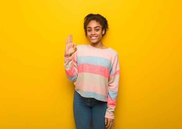 Giovane donna afroamericana nera con gli occhi azzurri allegro e fiducioso che fa gesto giusto
