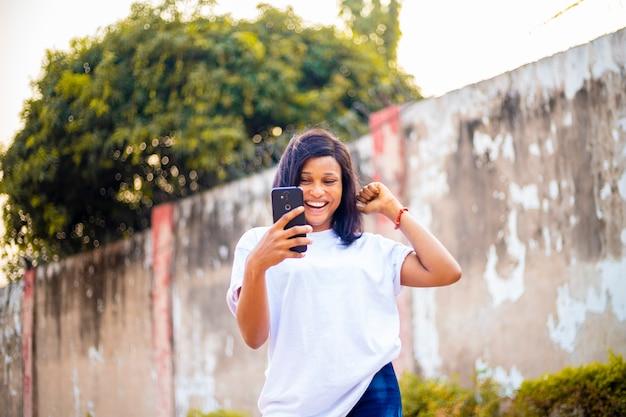 Giovane signora dell'africa nera che usa il suo telefono cellulare chattando in banca e guardando video online