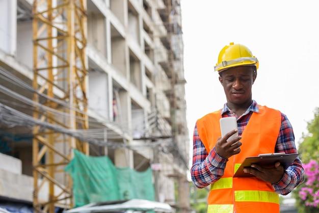 Giovane operaio edile uomo africano nero lettura negli appunti