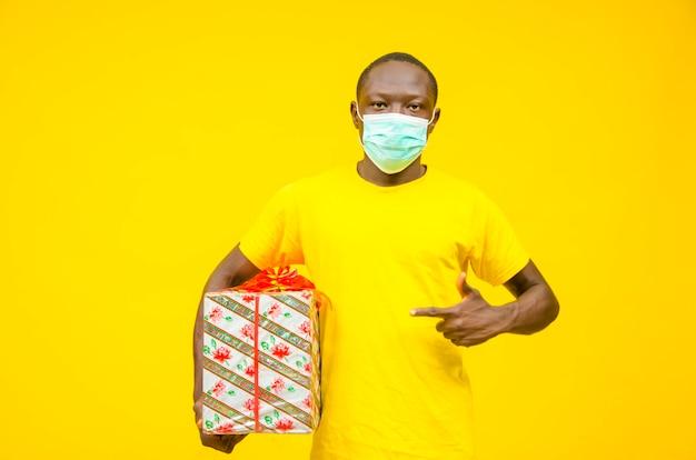 Giovane uomo africano nero fattorino in maschera medica che dà scatola regalo