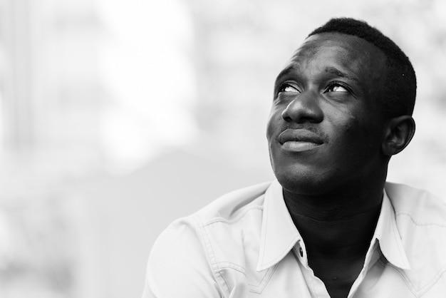 Giovane africano nero uomo seduto mentre pensa e cerca fuori dalla caffetteria contro la vista della natura e della città