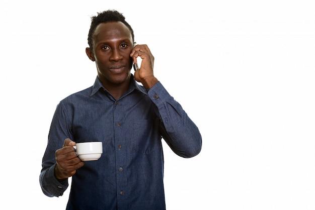 Giovane uomo dell'africa nera che parla sul telefono cellulare e che tiene bara