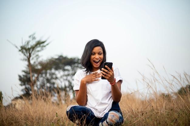 Giovane donna millenaria dell'africa nera che utilizza uno smartphone che chatta online con gli amici sui social media