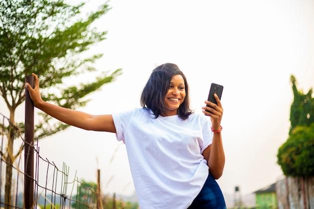 Giovani donne millenarie dell'africa nera che usano lo smartphone chattando online con gli amici sui social media