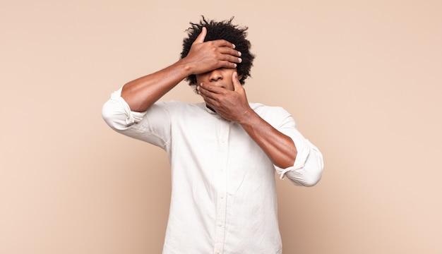 Giovane uomo afro nero che copre il viso con entrambe le mani dicendo no