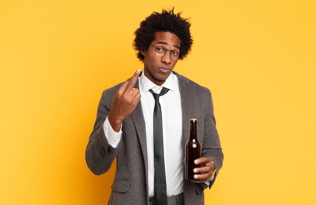 Giovane uomo afro nero che si sente arrabbiato, infastidito, ribelle e aggressivo, lancia il dito medio, reagisce