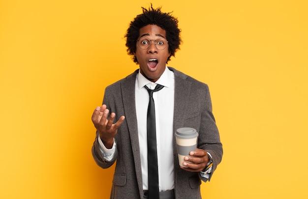 Giovane uomo afro nero che si sente estremamente scioccato e sorpreso, ansioso e in preda al panico, con uno sguardo stressato e inorridito