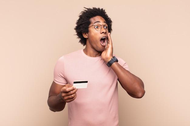Giovane uomo afro nero che si sente felice, eccitato e sorpreso, guardando di lato con entrambe le mani sul viso