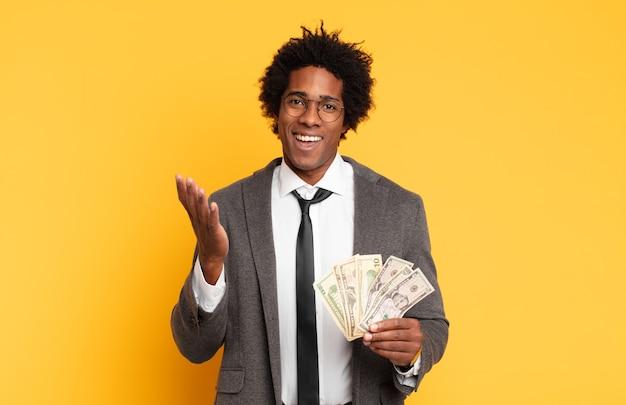 Giovane uomo afro nero che si sente felice, sorpreso e allegro, sorridente con atteggiamento positivo, realizzando una soluzione o un'idea