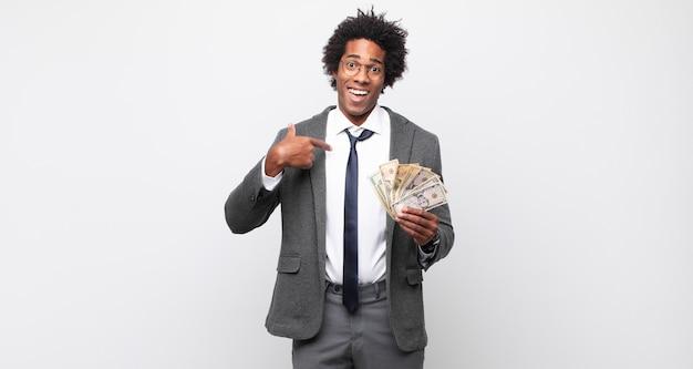 Giovane uomo afro nero che si sente felice, sorpreso e orgoglioso, indicando se stesso con uno sguardo eccitato e stupito